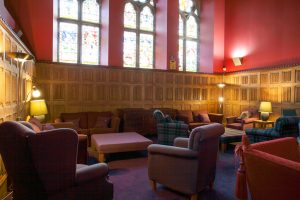 The Club Lounge with original oak paneling and stained glass windows
