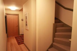 Hallway leading upstairs and to third bedroom or study.