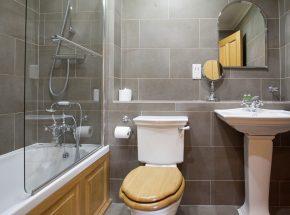Family bathroom has shower over bath