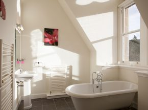 En suite bathroom has freestanding bath with views of the hills