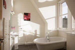 En suite bathroom has freestanding bath with views of the hills
