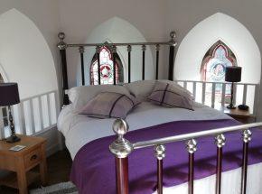 The bedroom has original stain glass windows