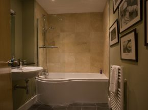Family bathroom with shower over a large bath