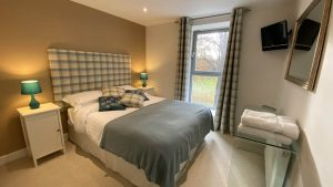 The master bedroom is welcoming and warm with views to the cricket pitch