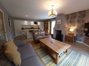 Living room, dining and kitchen area in Strathglass Cottage